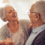 retired woman and man in the kitchen smiling