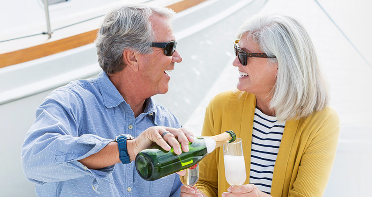 Mature couple enjoying a romantic date on a boat with champagne