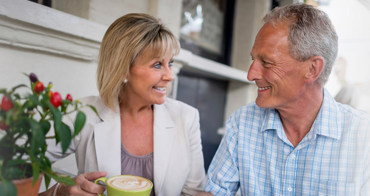 Smiling older couple outside with coffee