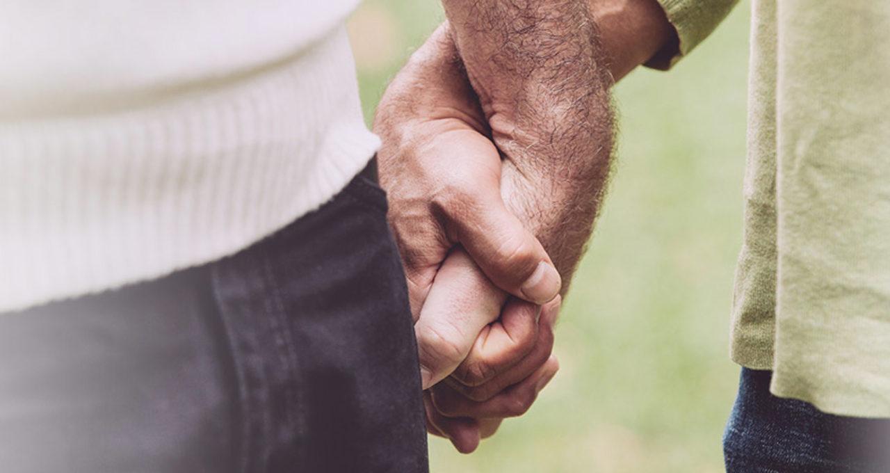 two older men holding hands