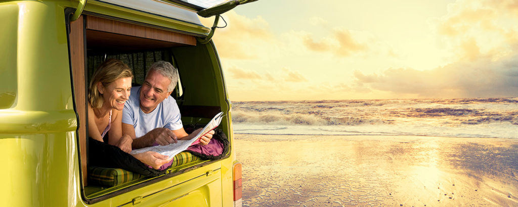older couple in a van by the sea