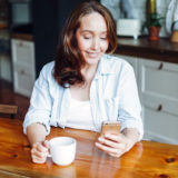 pretty older woman in her kitchen messaging over an online dating app
